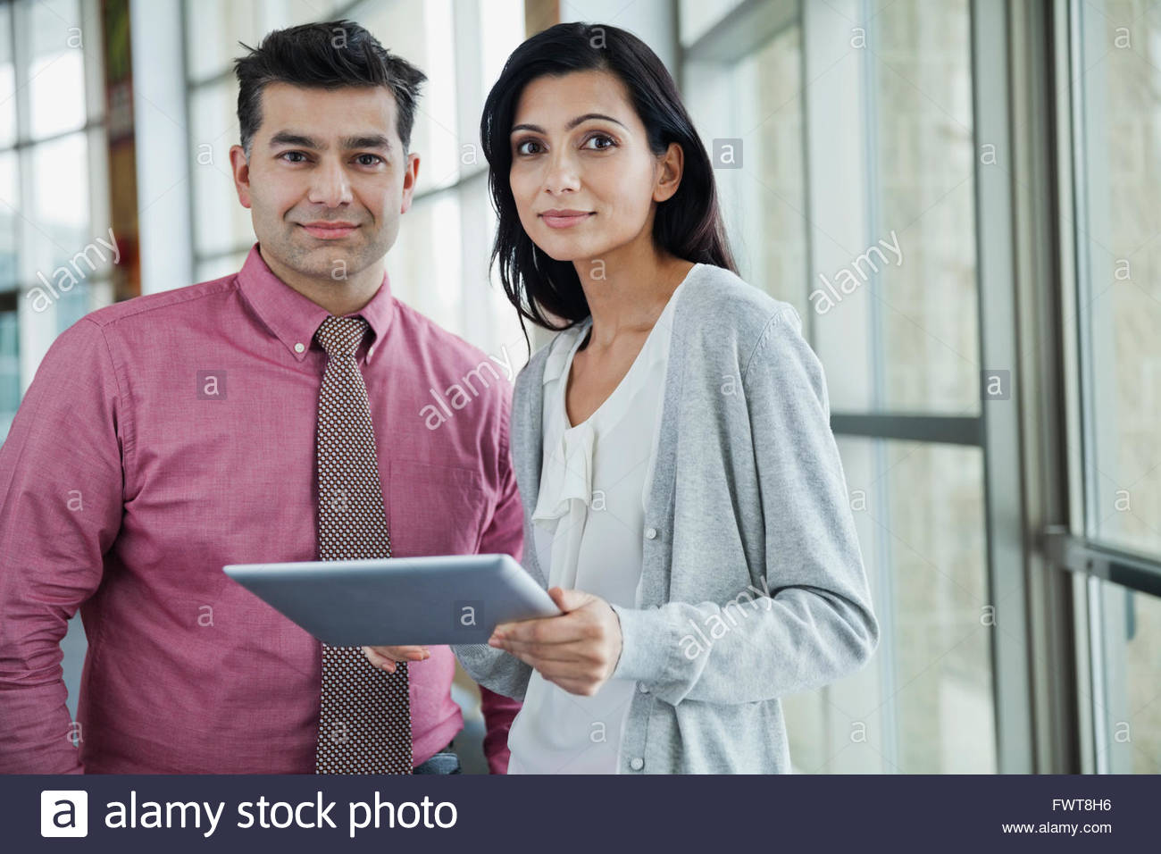 Portrait of businessman with female colleague holding digital tablet - Stock Image