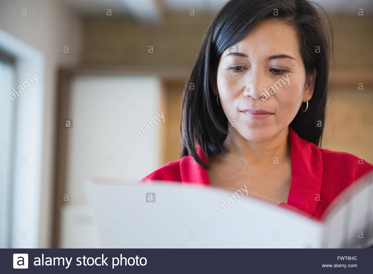 Mature businesswoman reading file in office - Stock Image