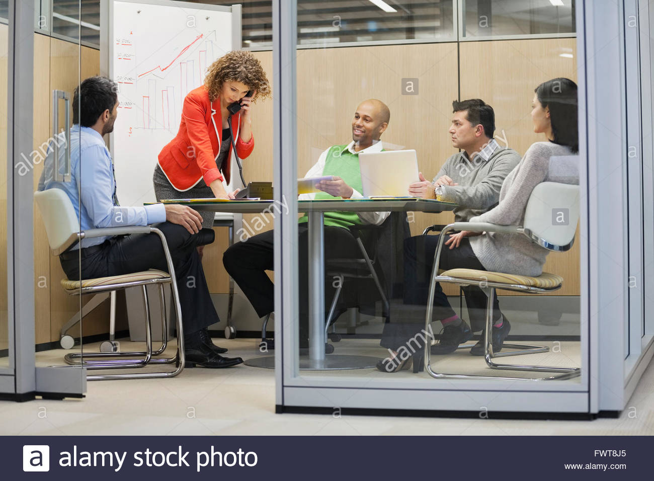 Businesswoman using telephone with colleagues in board room - Stock Image