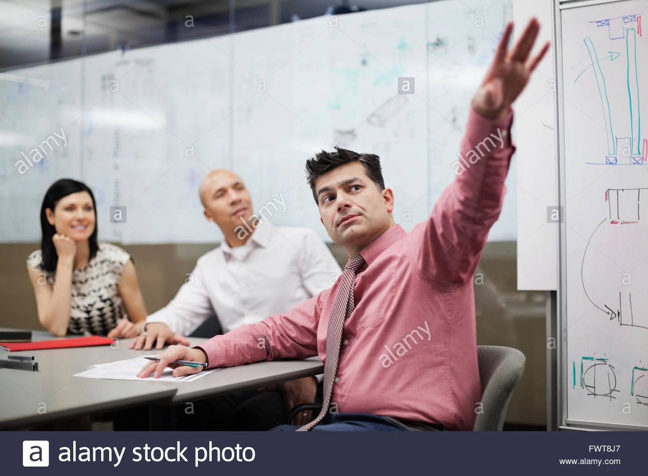Mature businessman gesturing to white board presentation - Stock Image