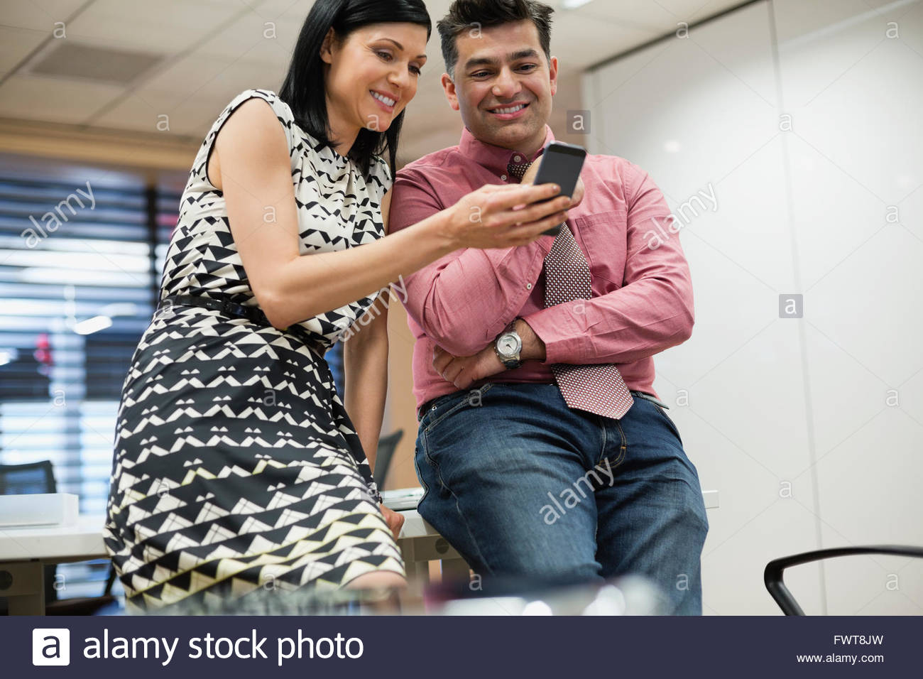 Business colleagues using mobile phone together in office Stock Photo