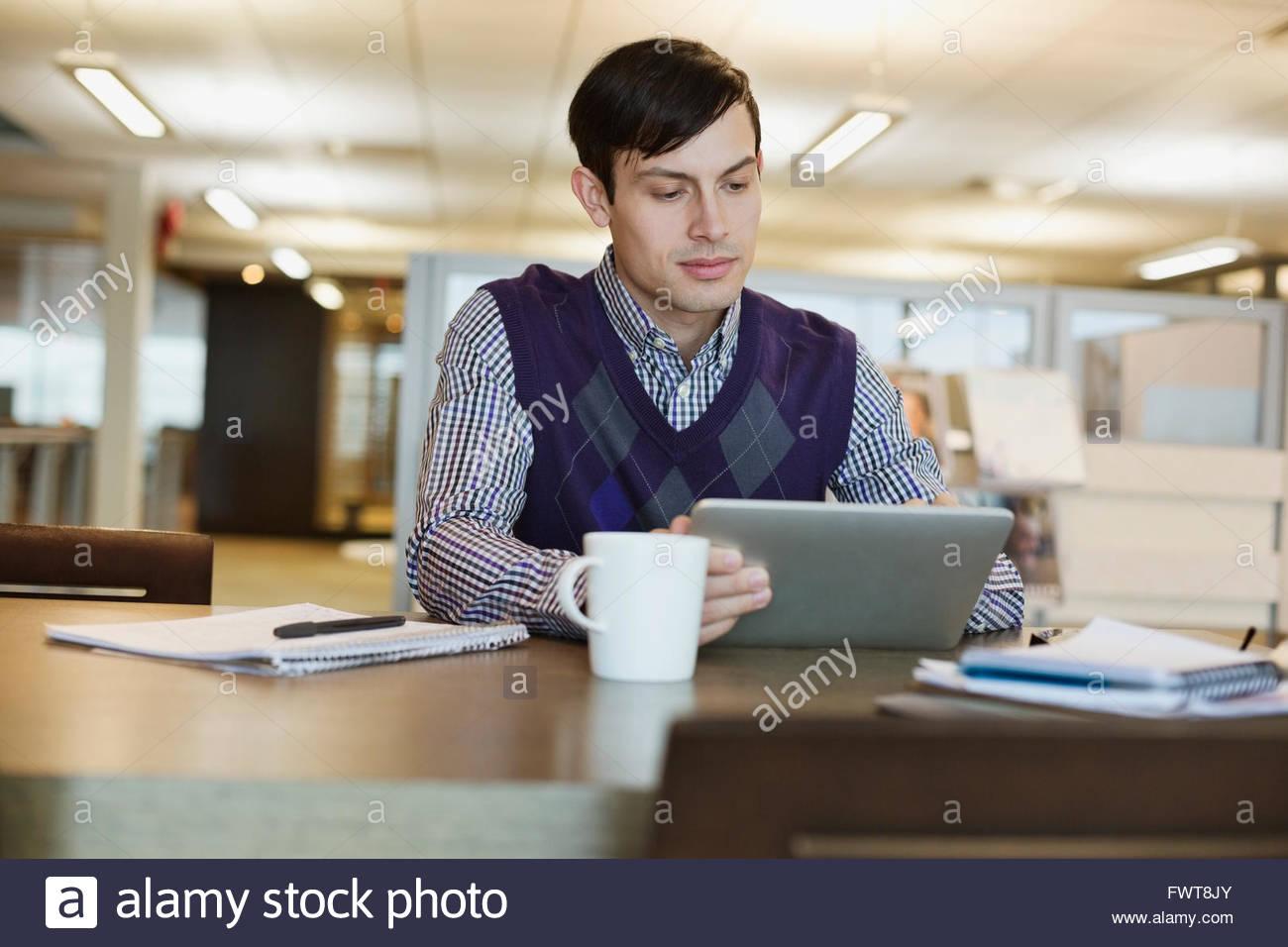 Businessman using digital tablet at office desk - Stock Image