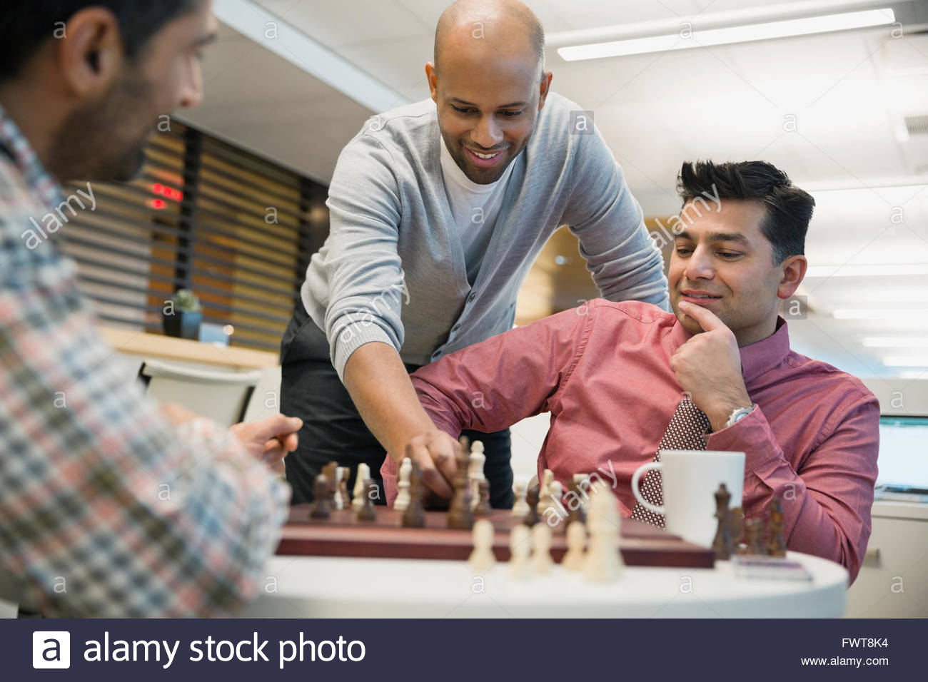 Businessmen playing chess at coffee table in office - Stock Image