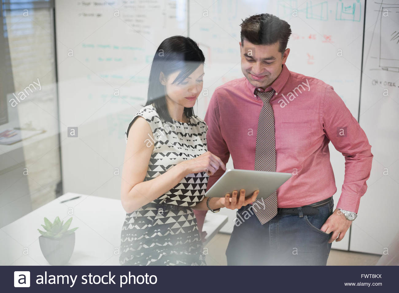 Coworkers sharing a digital tablet in meeting room - Stock Image