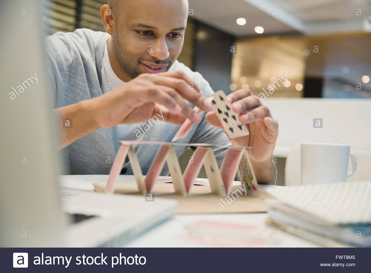 Businessman building a house of cards in office Stock Photo