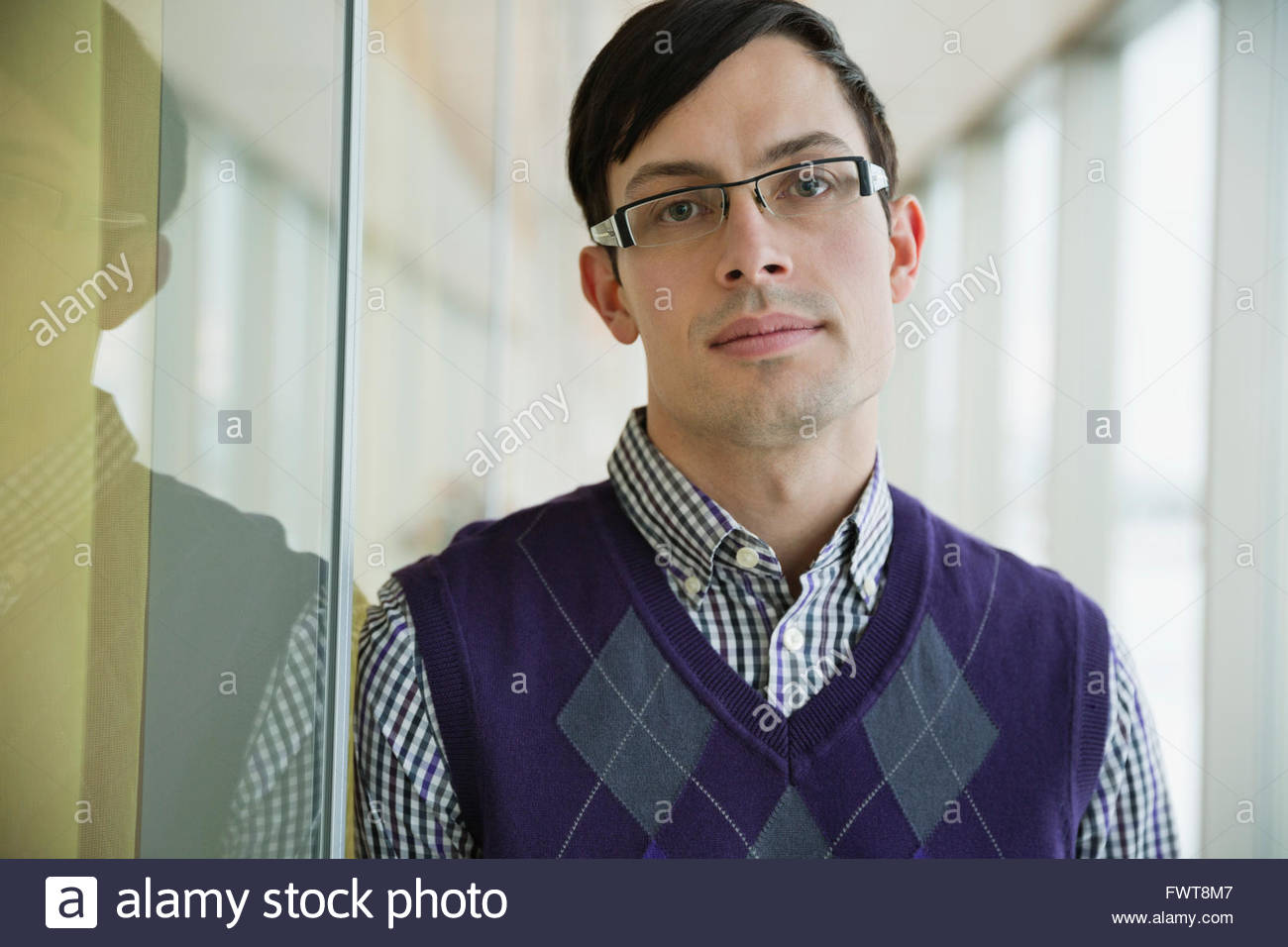 Portrait of handsome young businessman in office - Stock Image