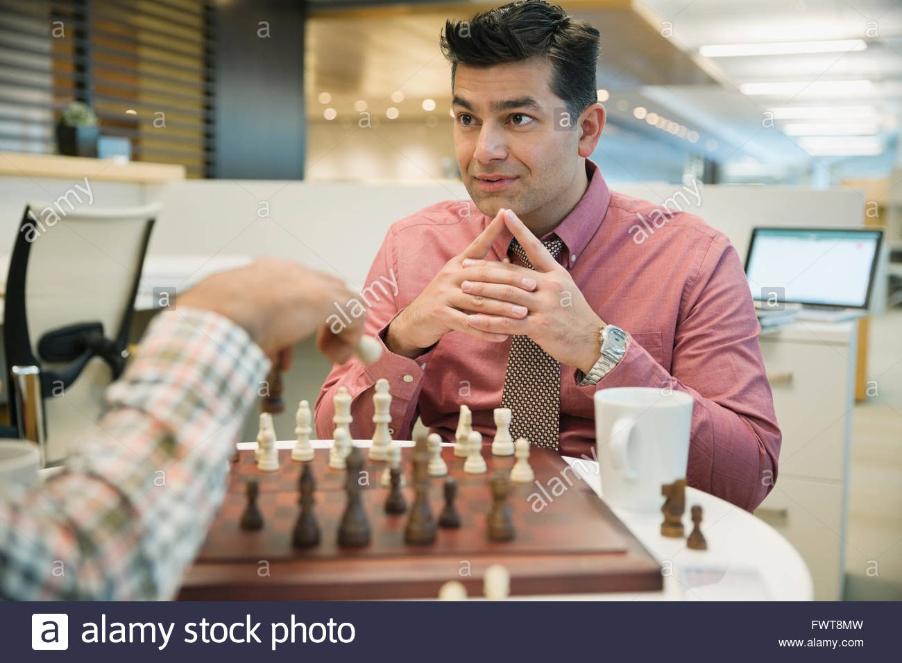 Businessman playing chess with coworker in office - Stock Image