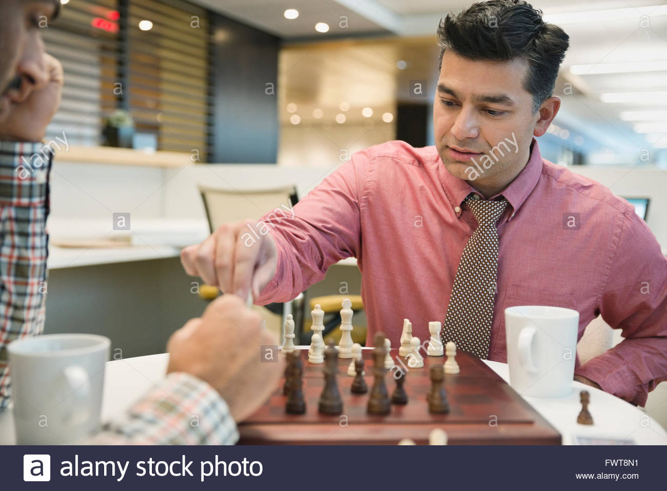 Businessman playing chess with coworker at table - Stock Image