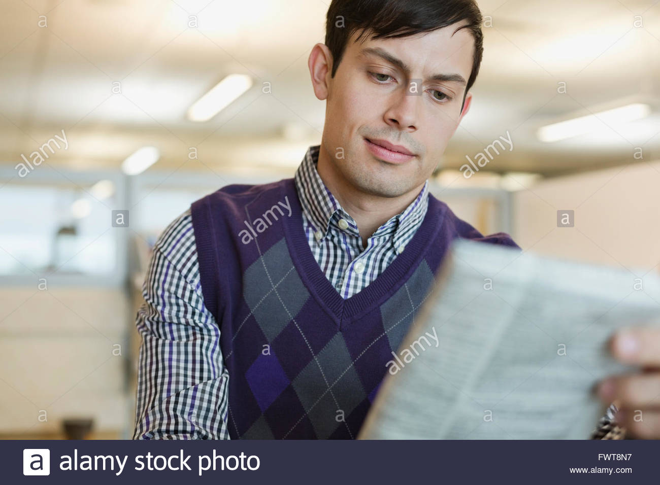 Businessman reading newspaper in office - Stock Image