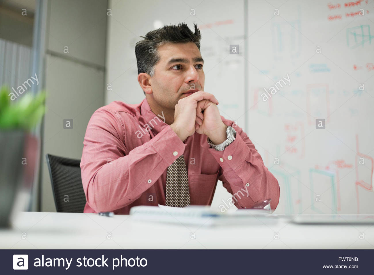 Mature businessman sitting at office desk in board room Stock Photo