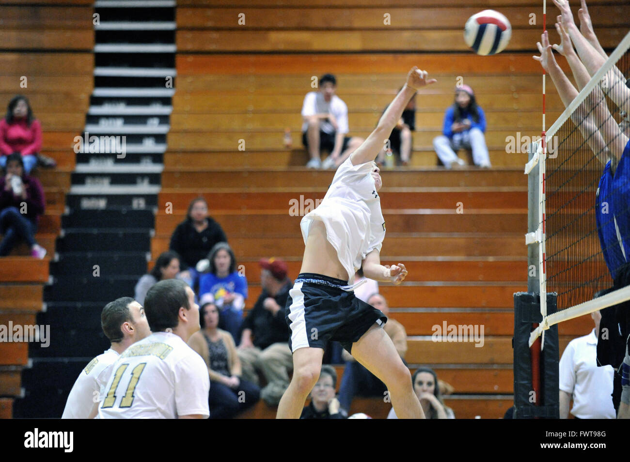 High school player rising above the floor in an effort to deliver a point-winning kill shot. USA. - Stock Image