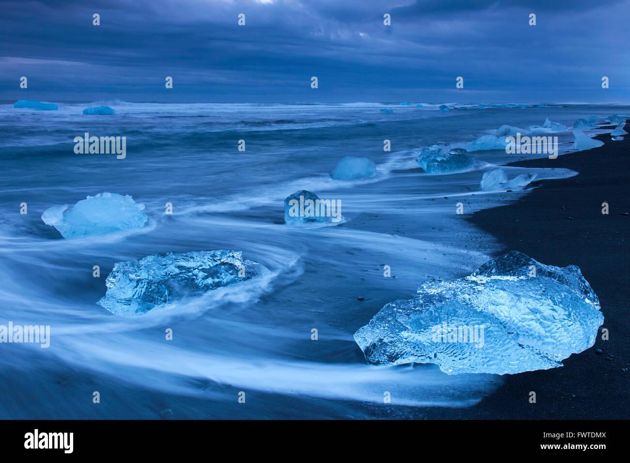Melting blocks of ice washed on beach along the Atlantic Ocean coastline at Breidamerkursandur black sands in winter, - Stock Image