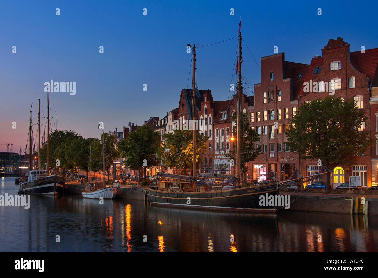 Museums harbour at night with traditional sailing ships berthed at the Untertrave in the Hanseatic town Lübeck, - Stock Image