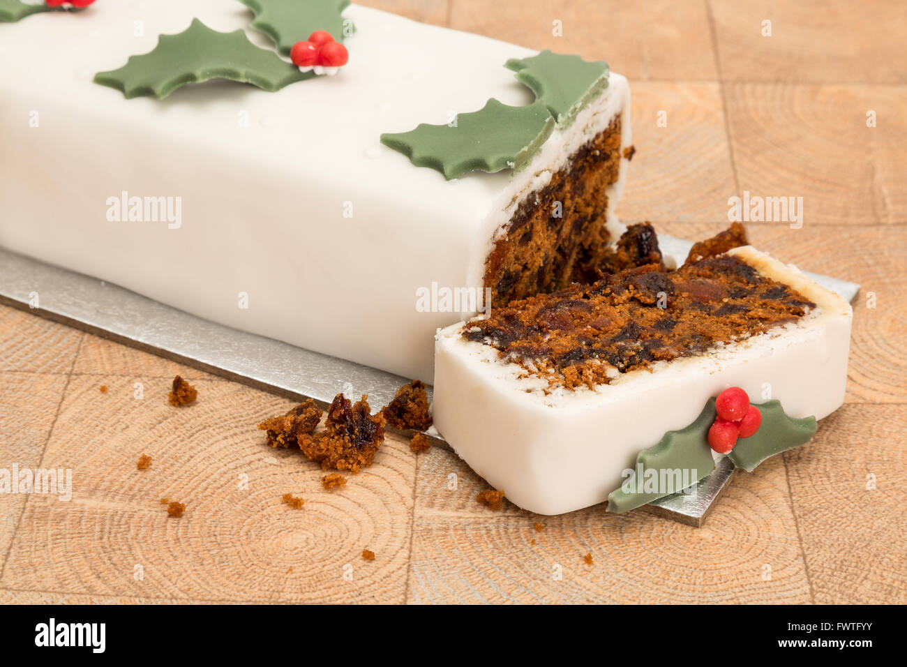 Christmas cake with a slice taken out, shallow depth of field - Stock Image