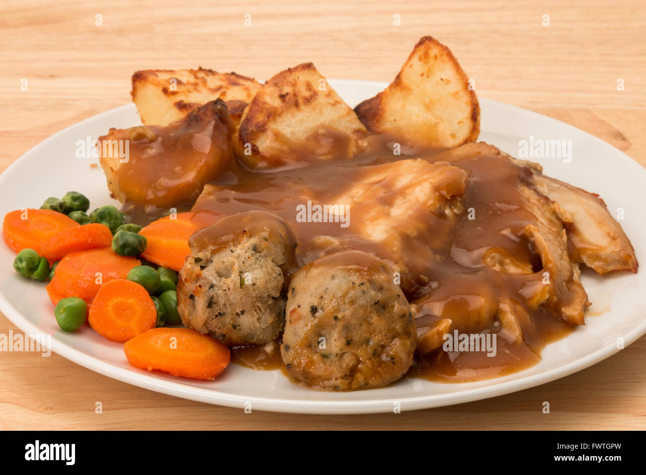 A roasted chicken dinner with carrot and peas, sage and onion stuffing balls, and gravy. - Stock Image