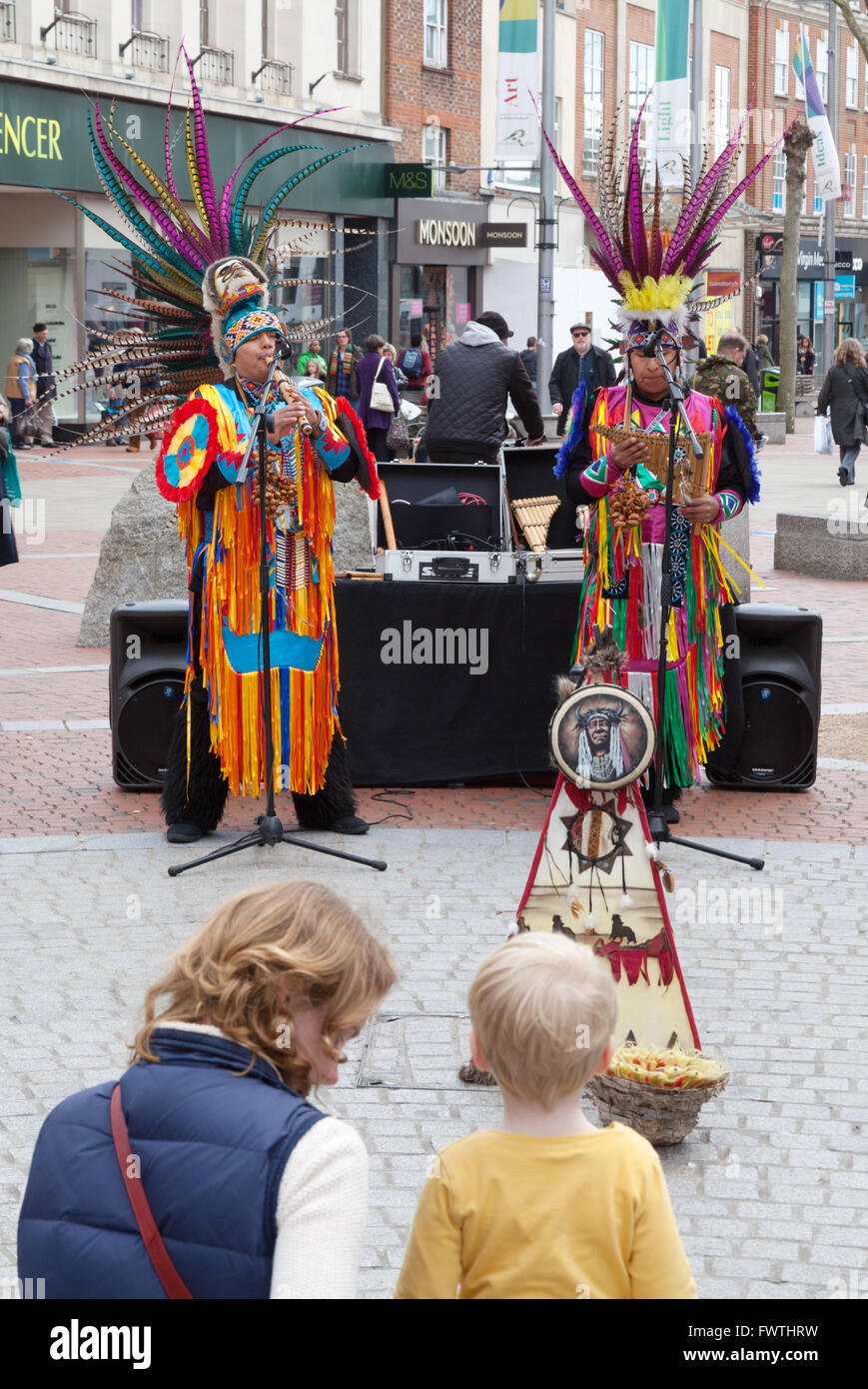 Mother and child listening to Peruvian south american buskers street music, Broad Street, Reading Berkshire UK Stock Photo