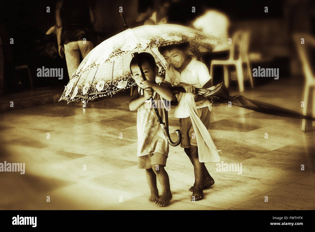 Kids are playing with an umbrella on the Chinese Cemetery, where homeless people are living. Cebu City, Philippines. - Stock Image