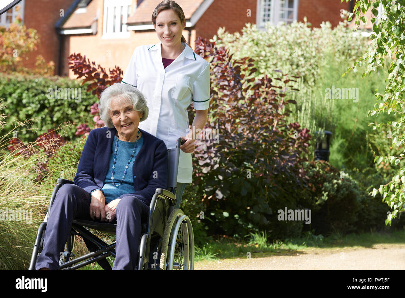 Portrait Of Carer Pushing Senior Woman In Wheelchair - Stock Image