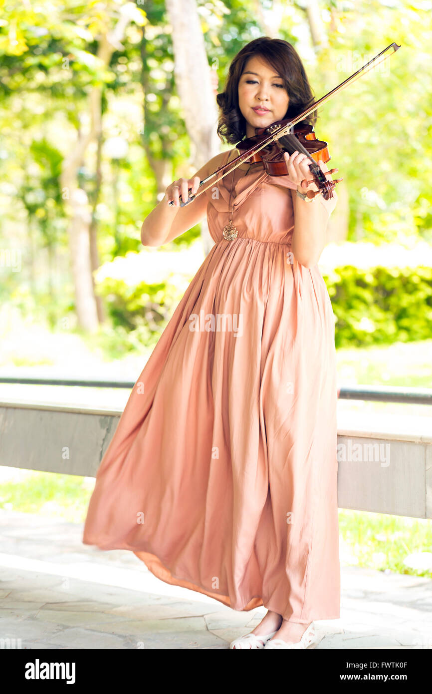 Young woman playing violin in garden - Stock Image