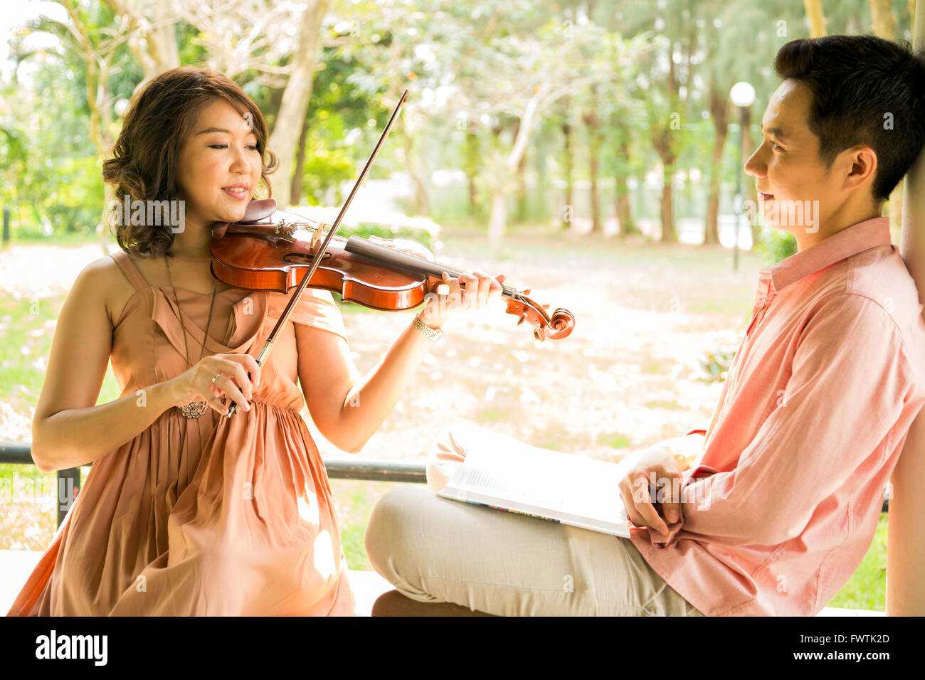 Young woman playing violin with her boyfriend in garden - Stock Image