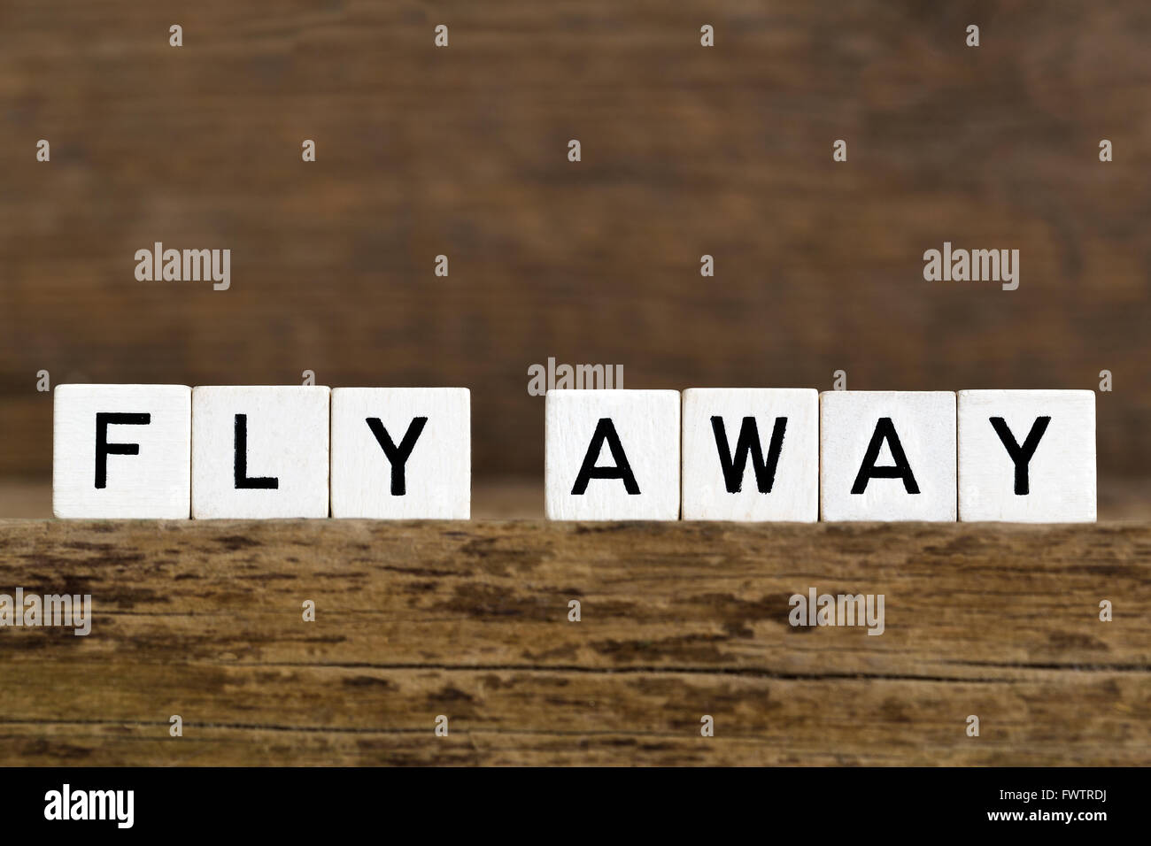 The words fly away written in cubes on wooden background - Stock Image