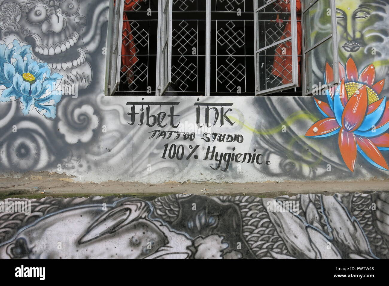 'Tibet TDK Tattoo Studio 100% Hygienic' hand painted sign or advertising on wall with graffiti artwork illustrating - Stock Image