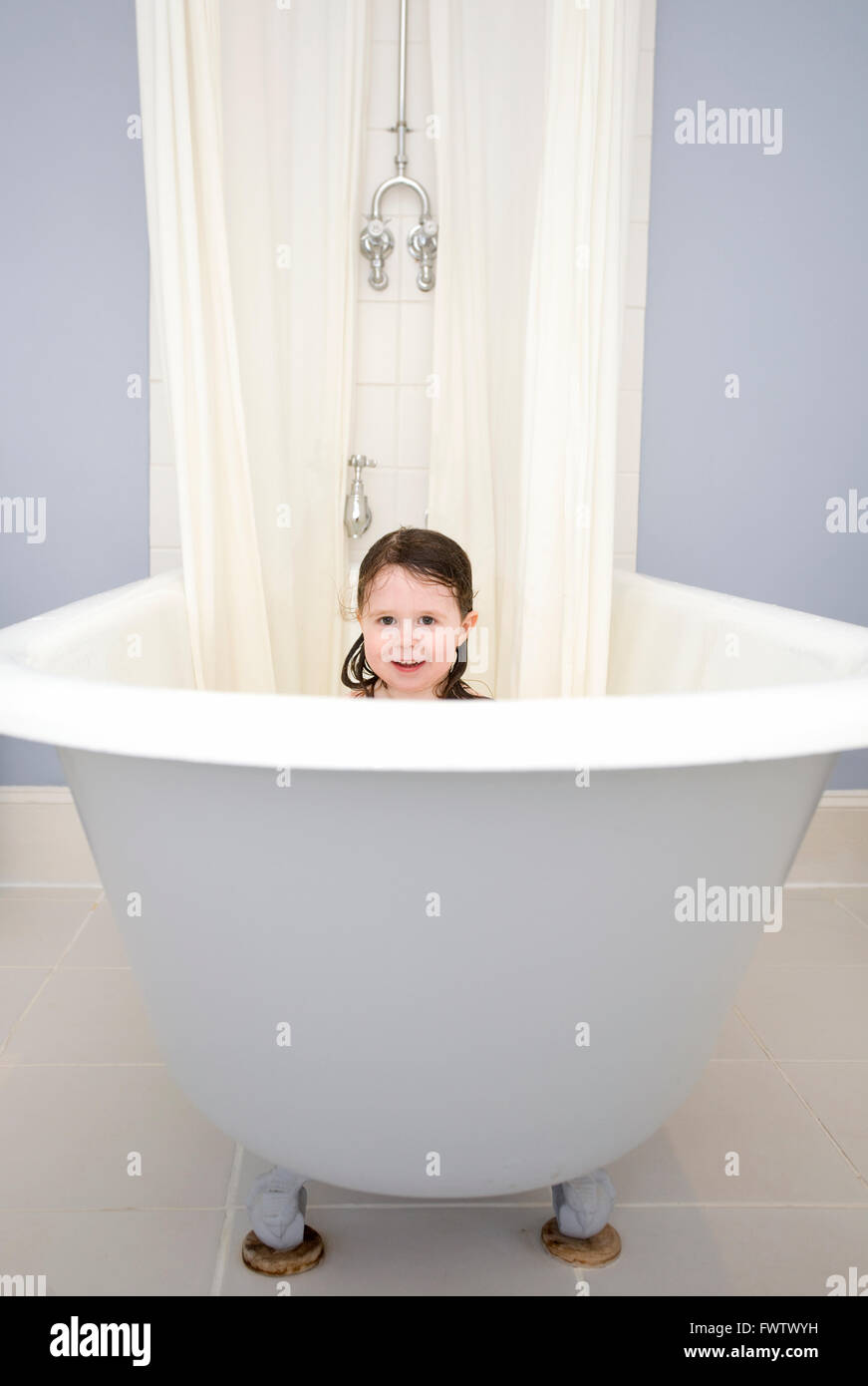 toddler sat in large cast iron bath tub Stock Photo: 101965461 - Alamy