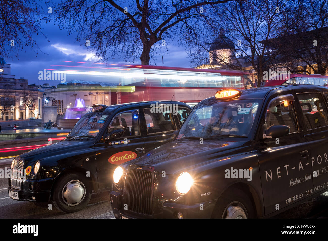 Two taxis and a bus at London's Trafalgar Square at Dusk. - Stock Image