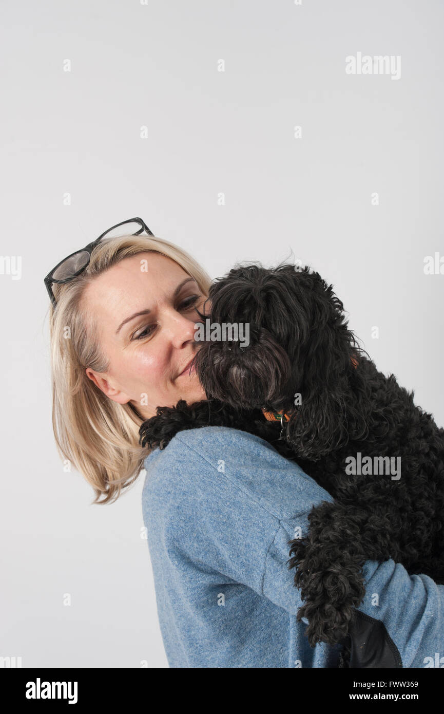 An attractive middle aged woman with her black cockapoo dog - Stock Image