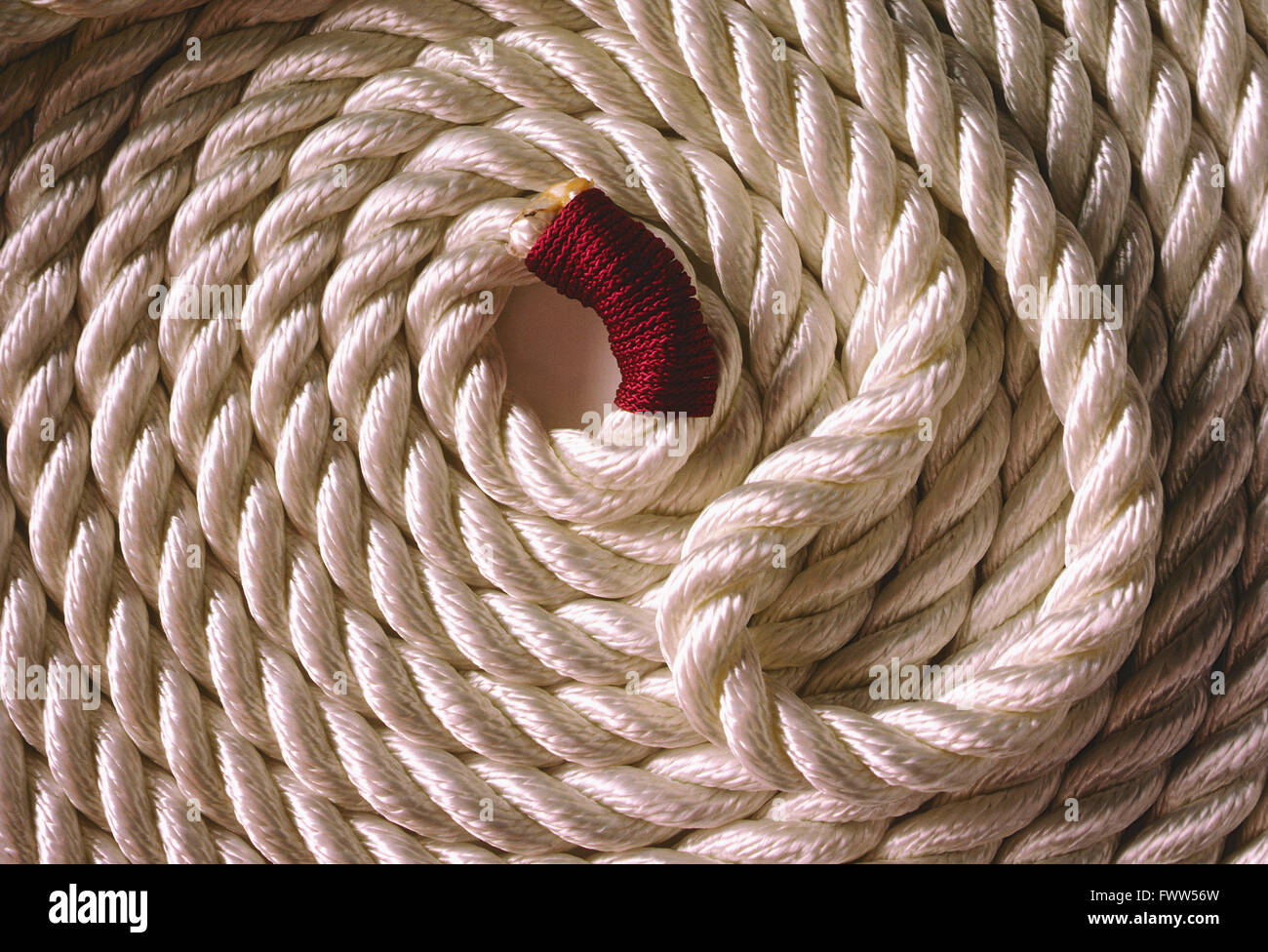 Heavy coiled white marina rope - Stock Image