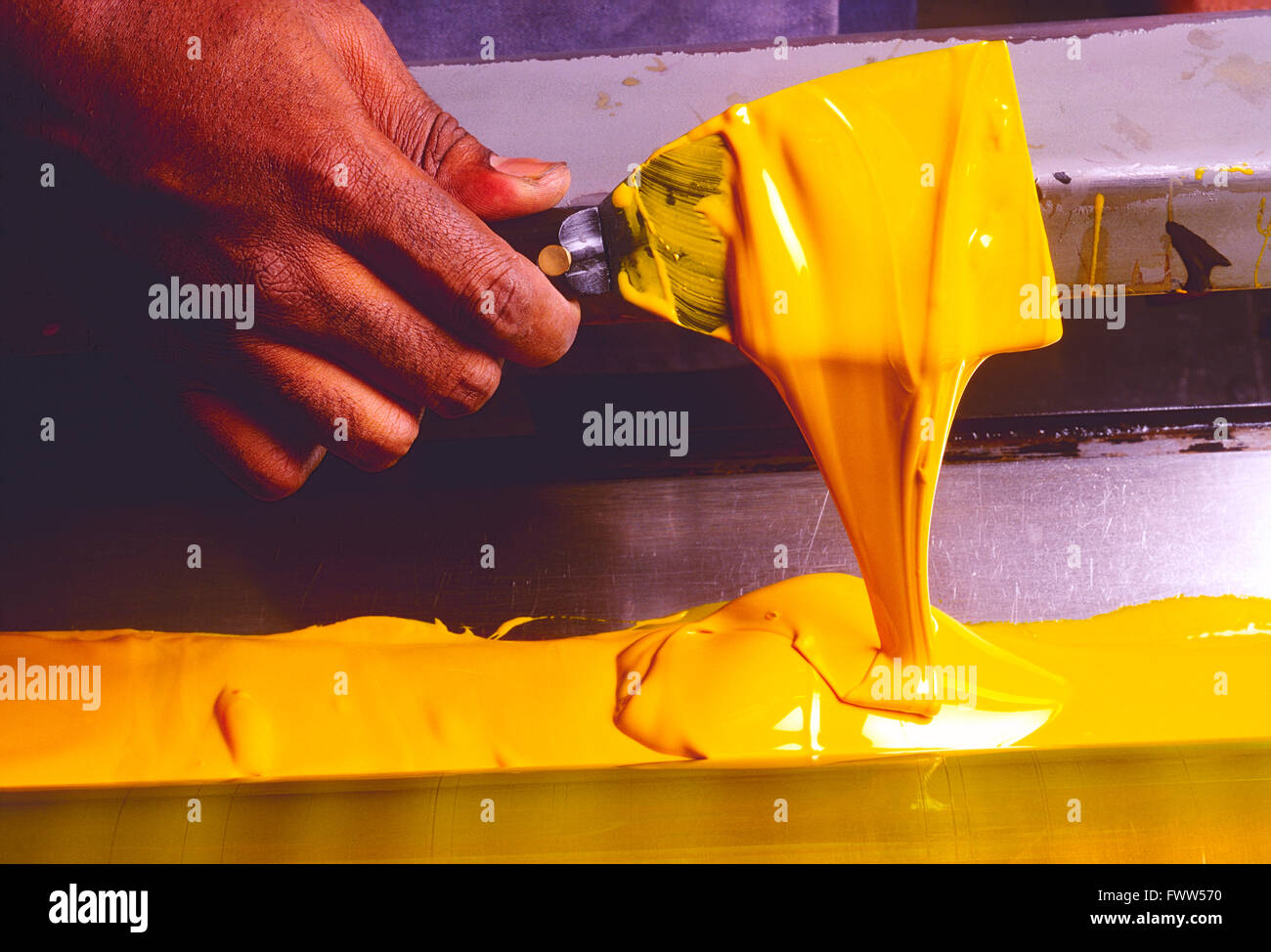 Close-up of African American printer's hand spreading printing ink with a blade hand tool - Stock Image