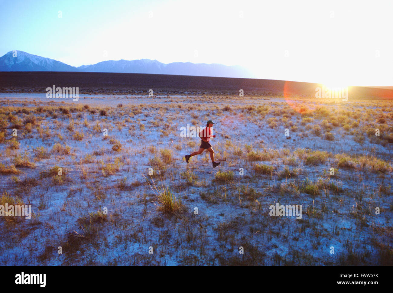Fit young male athlete trail runner in Sierra Nevada foothills at sunset - Stock Image