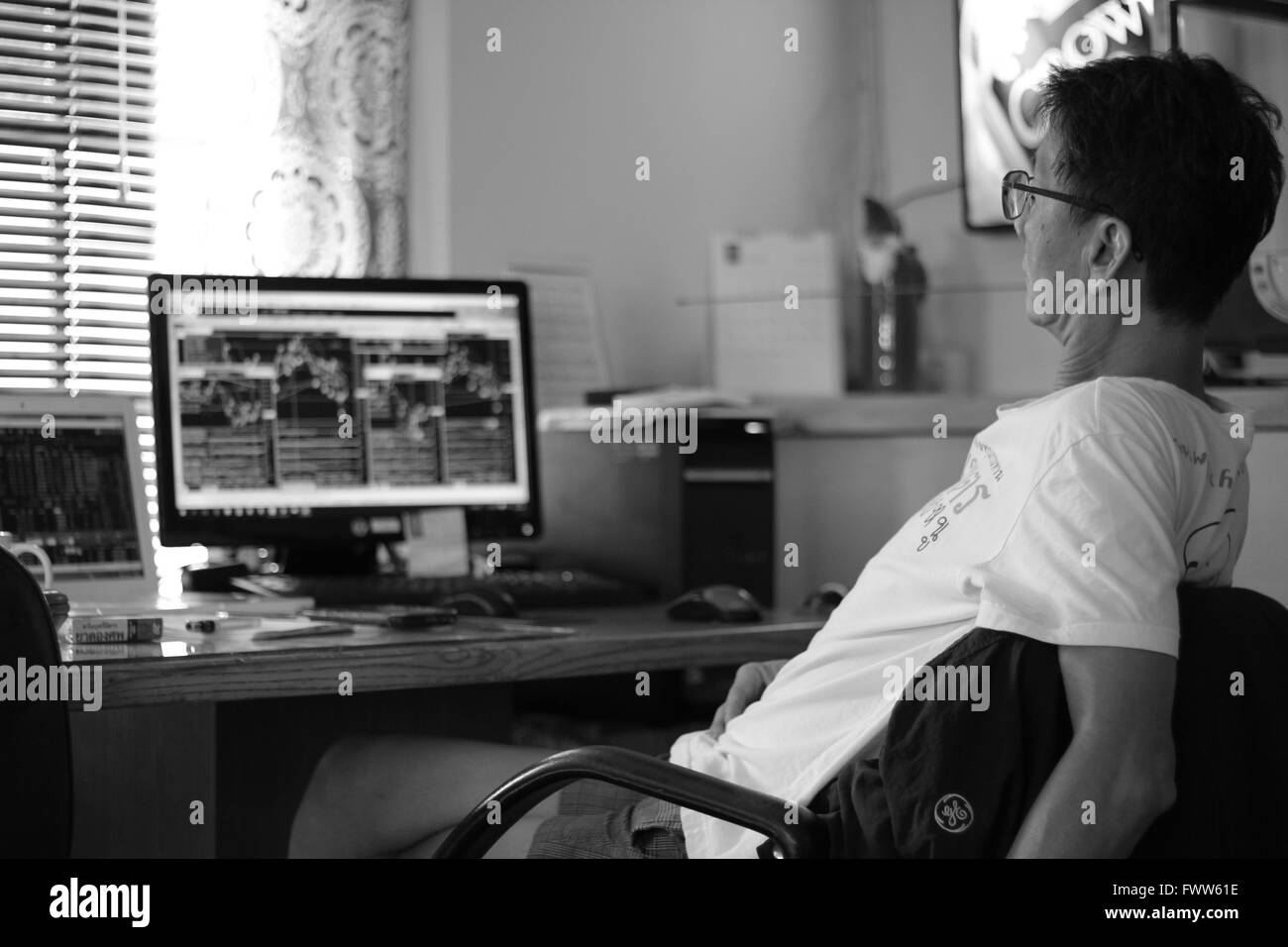 Asian man working at a computer - Stock Market day trading - Stock Image