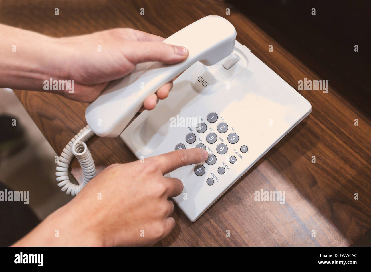 Human hands holding telephone handle and dialing on wooden table . - Stock Image