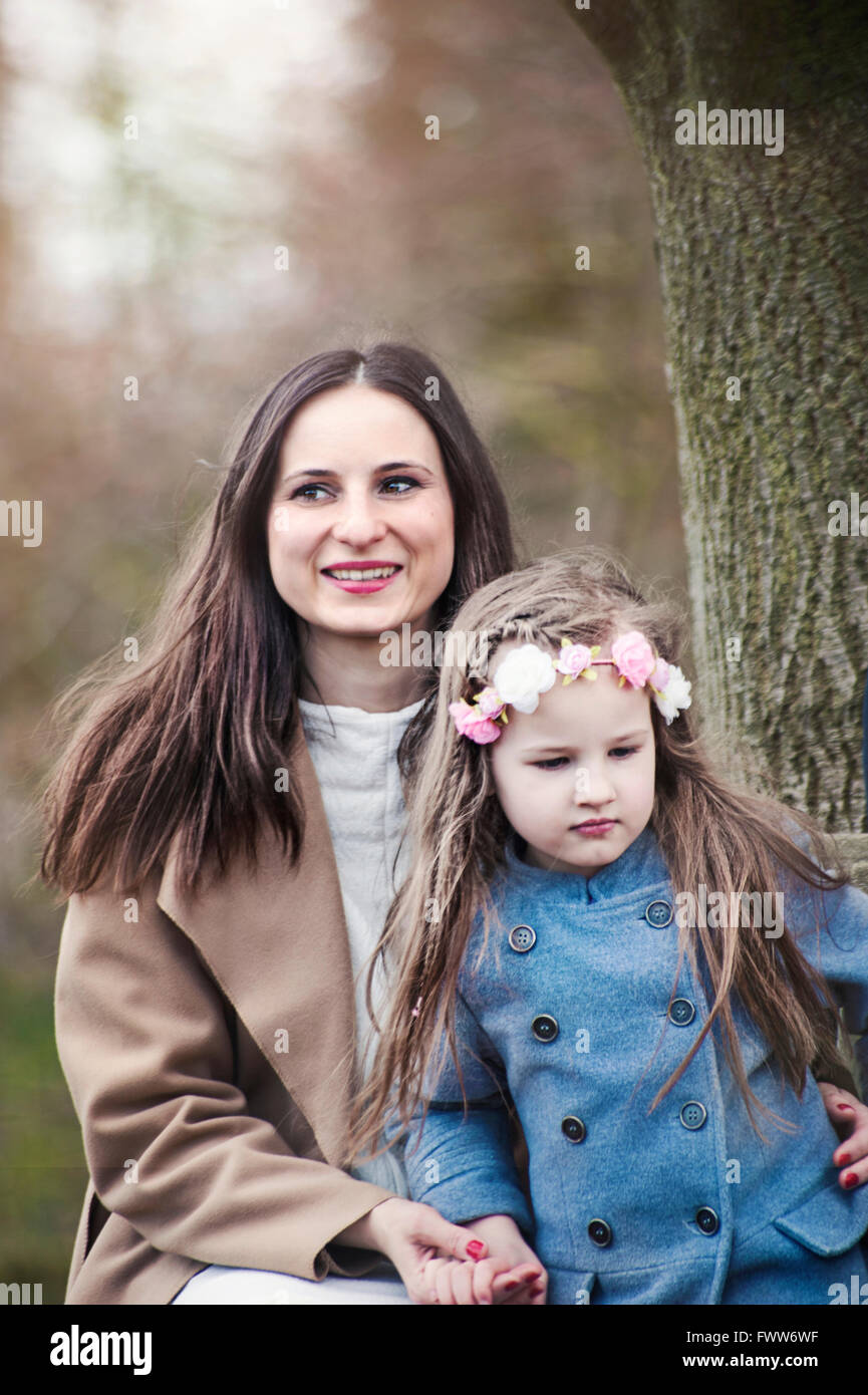 young woman sitting with her small daughter under the tree - Stock Image