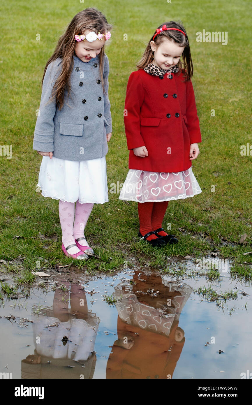 two little sisters standing by the puddle looking at water reflection - Stock Image