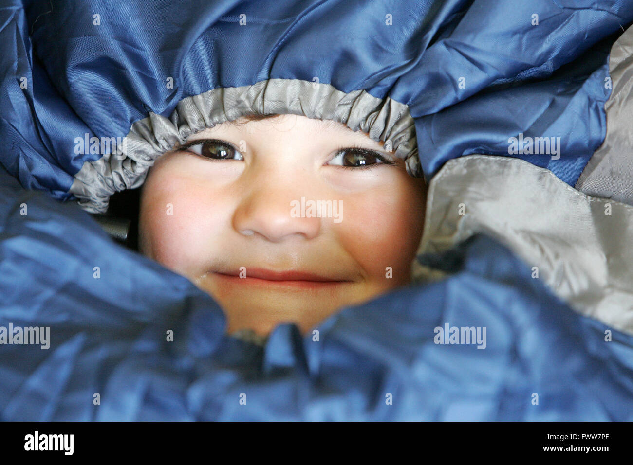 Young boy all tucked up in a sleeping bag - Stock Image