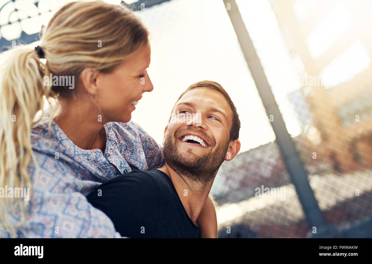 Couple Smiling At Each Other, Woman On Mans Back - Stock Image