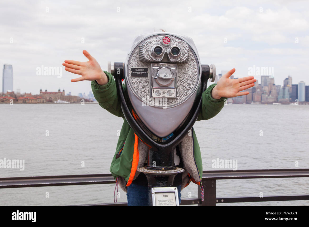 Six year old boy behind coin operated binoculars, Liberty island, New York, United States of America. - Stock Image