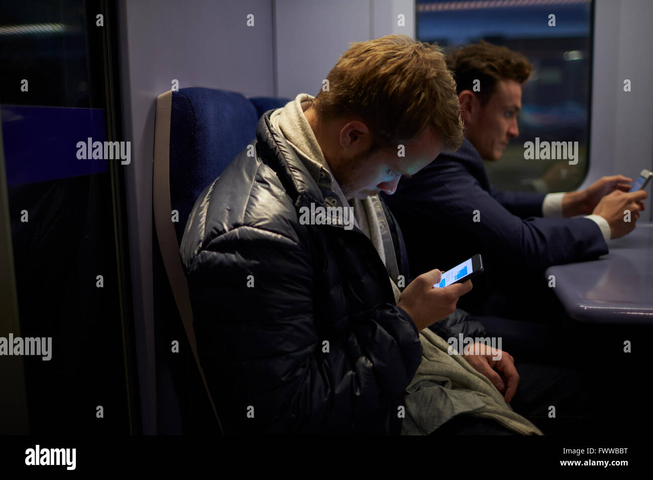 Man Sitting In Train Carriage Sending Text Message - Stock Image