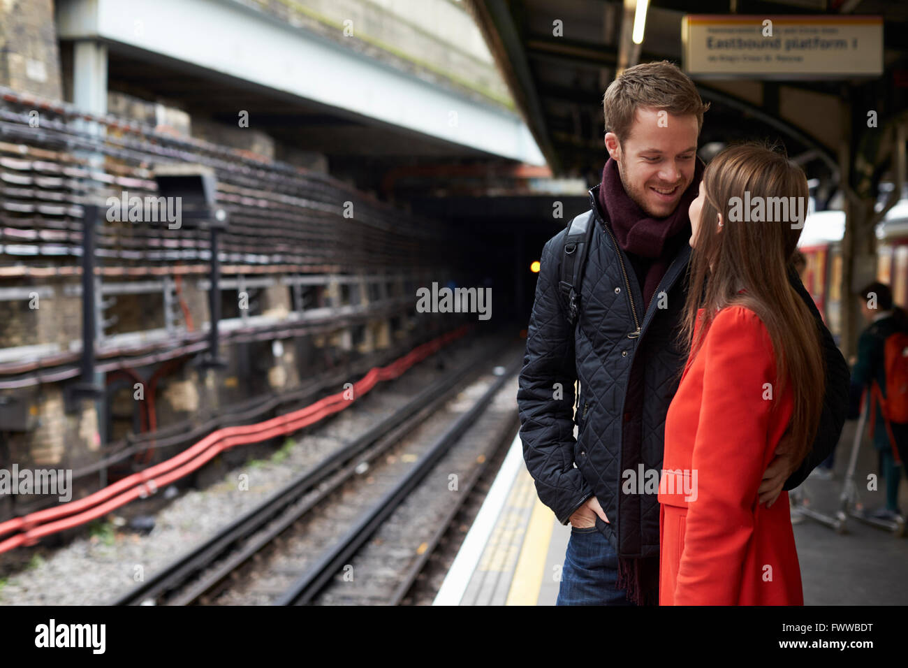 Young Couple Standing On Railway Station Platform Together - Stock Image