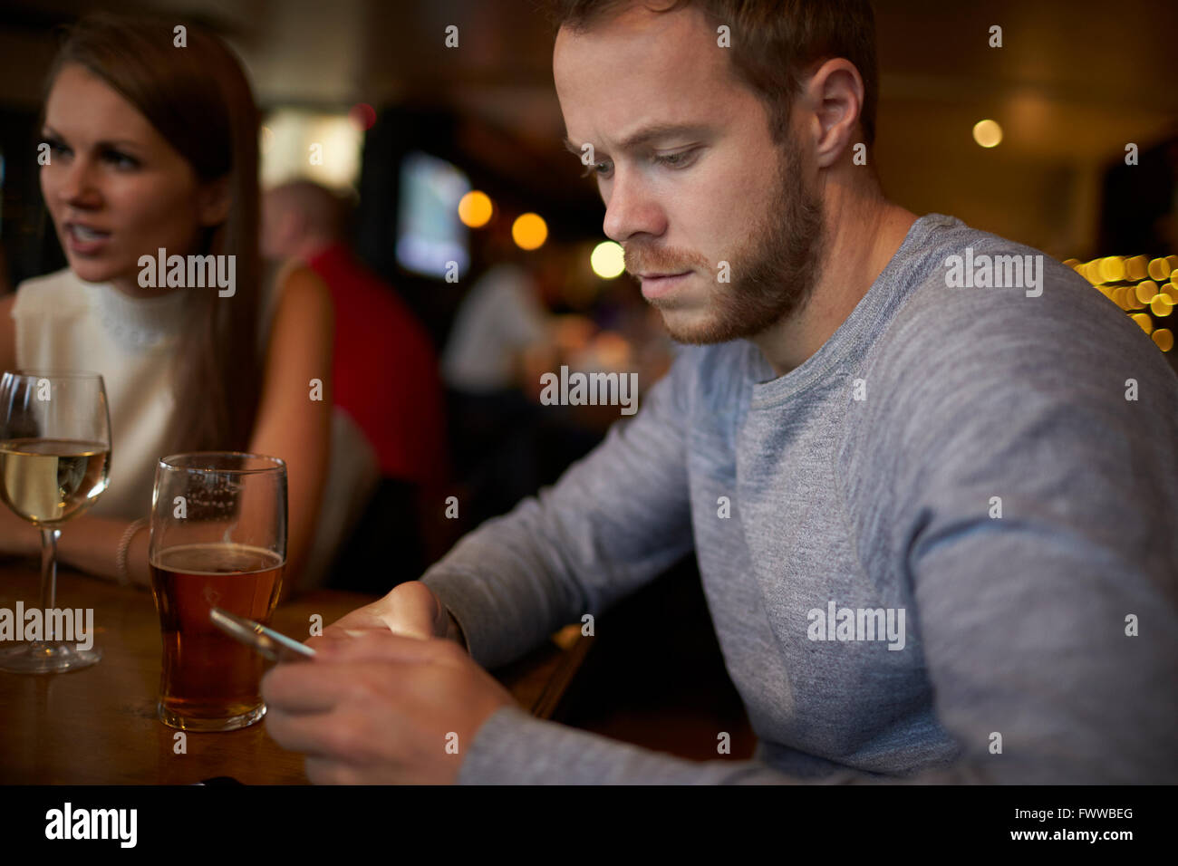 Young Man Sitting In Bar Sending Text Message - Stock Image