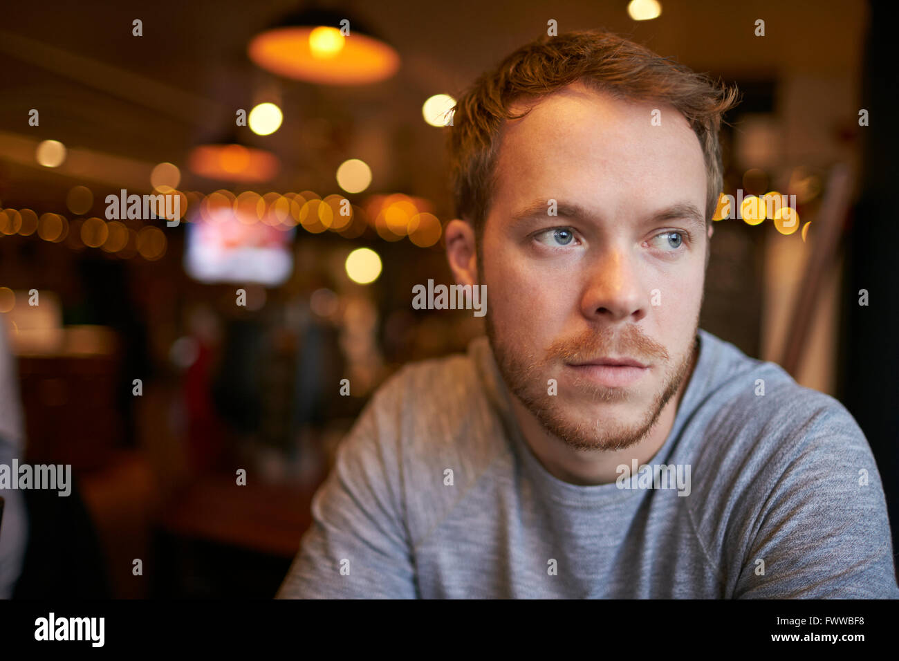 Young Man Sitting Alone In Bar - Stock Image