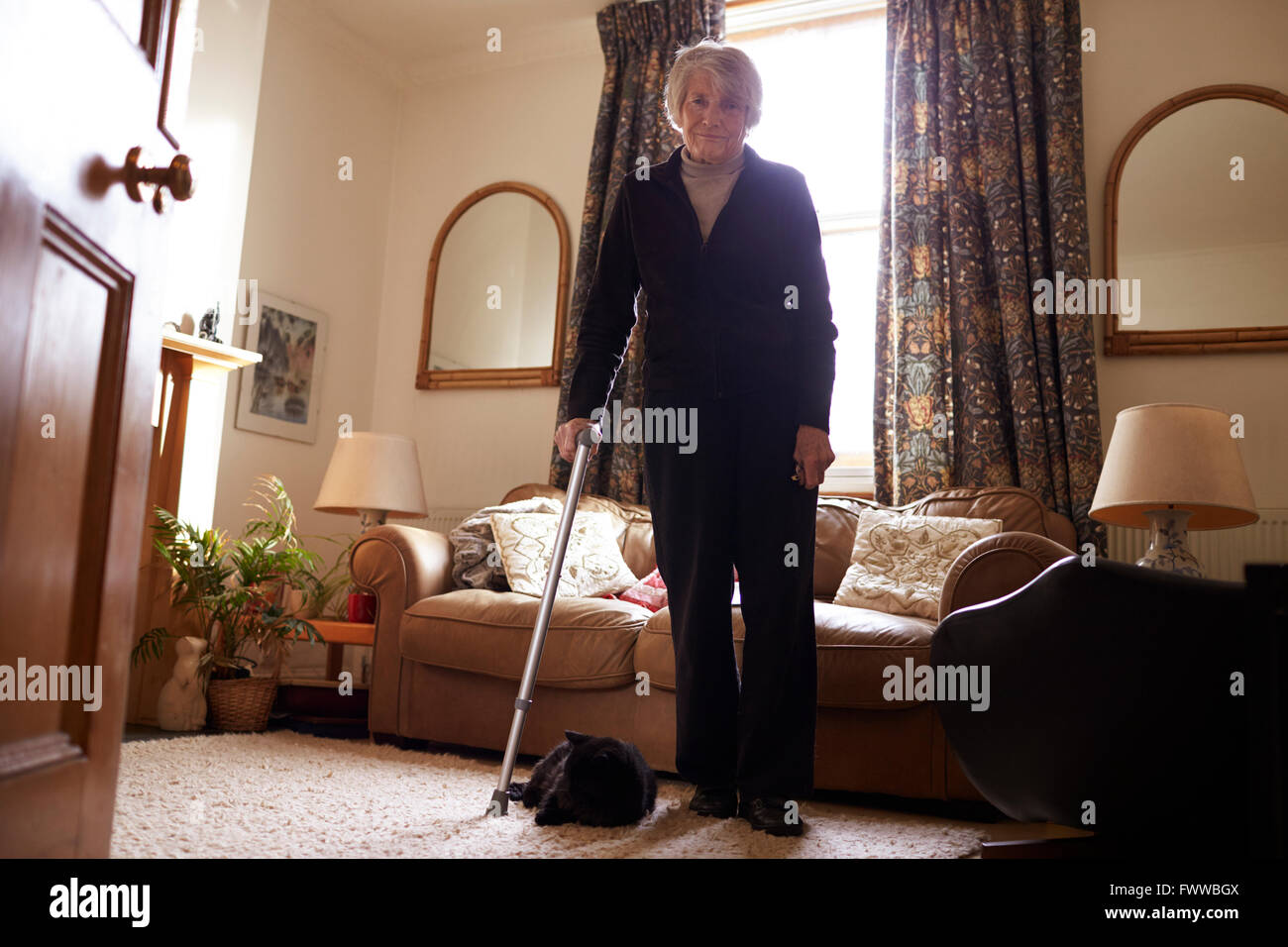 Portrait Of Senior Woman With Crutch Standing In Lounge Stock Photo