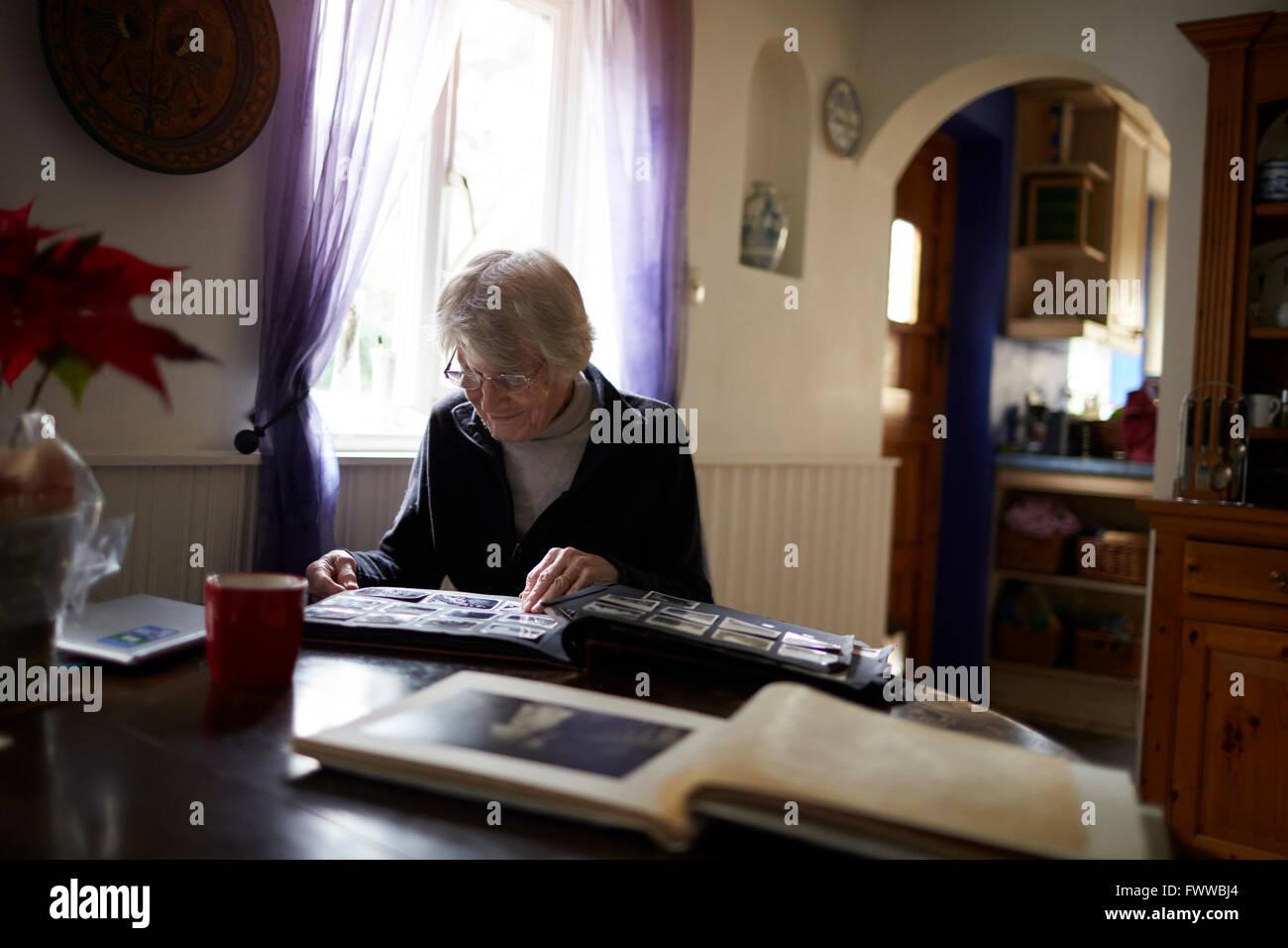 Senior Woman Looking Through Photo Album At Home - Stock Image