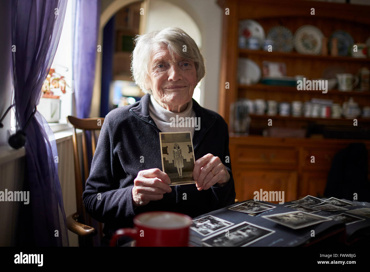 Senior Woman Holding Photo Of Her Younger Self - Stock Image