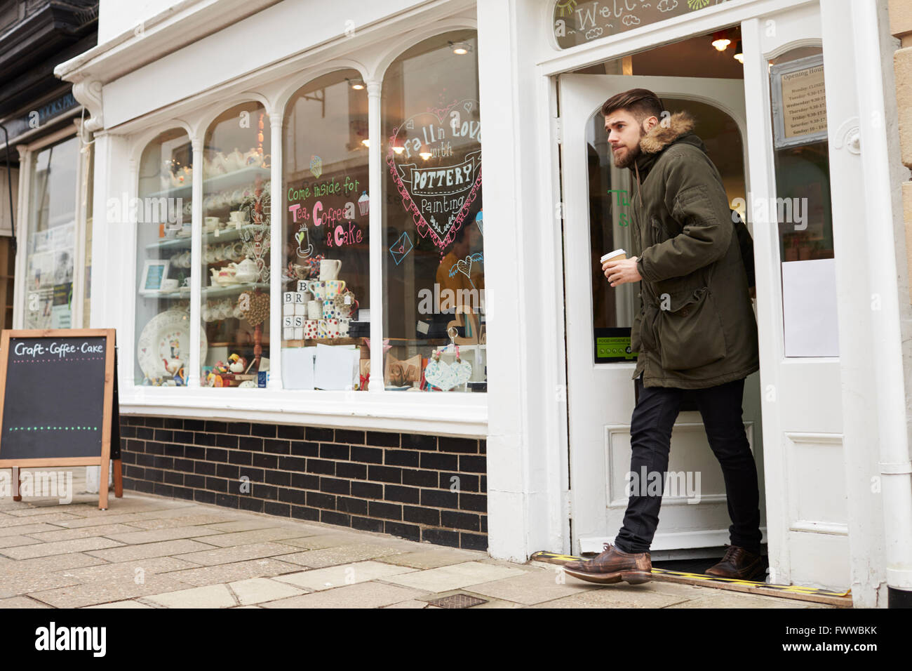 Male Customer Coming Out Of Cafe With Takeaway Coffee Stock Photo