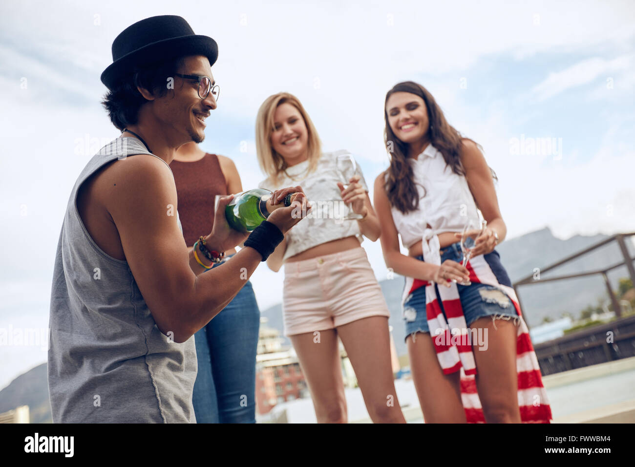 Outdoor shot of young man opening a bottle of champagne with female friends standing in background by the pool. - Stock Image