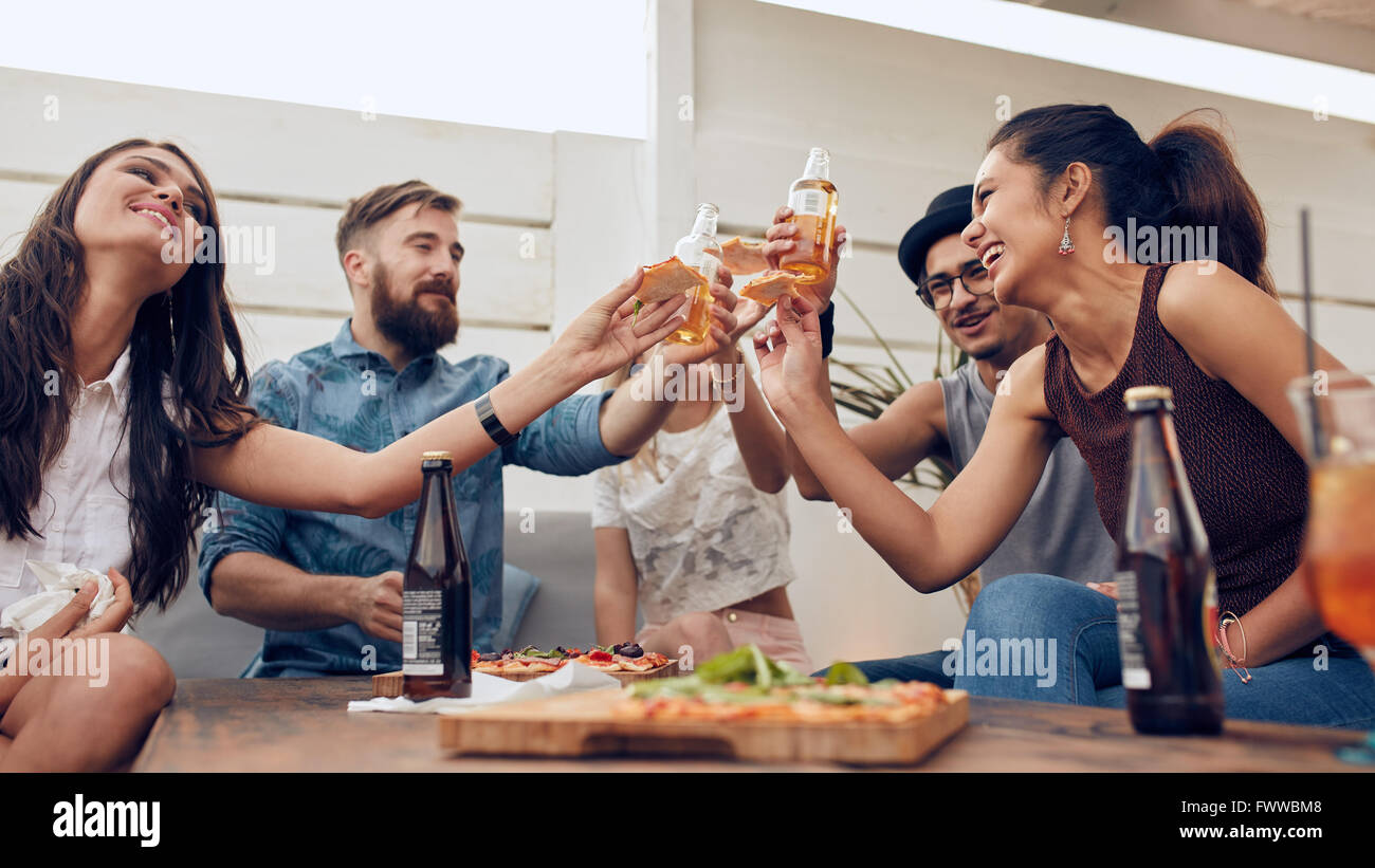 Group of friends toasting beers in a party while sitting around table. Multiracial friends hanging out on rooftop - Stock Image