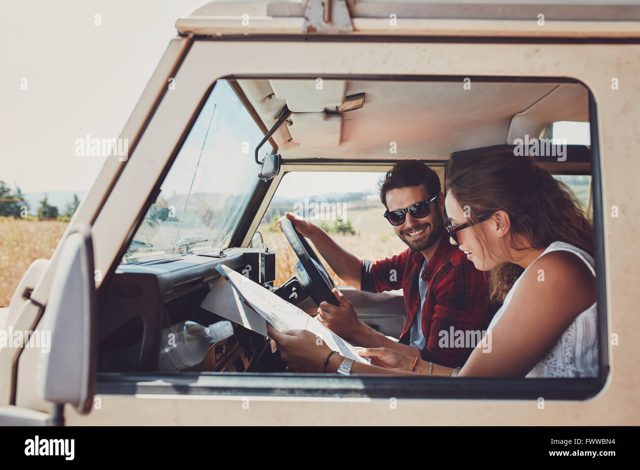 Man and woman on a road trip and reading a map together while seated inside their car. Happy young couple going - Stock Image